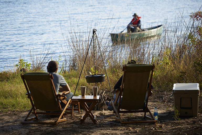 Two people at a campsite sitting in chairs next to a lake