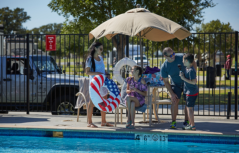 Two adults and two children at a table next to a pool.