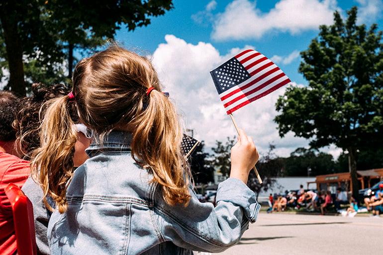 little girl holding american flag