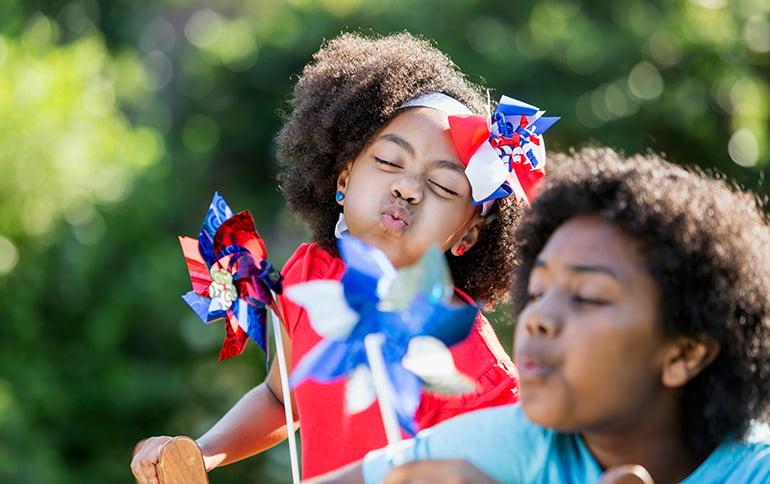 2 children blowing on patriotic pinwheels