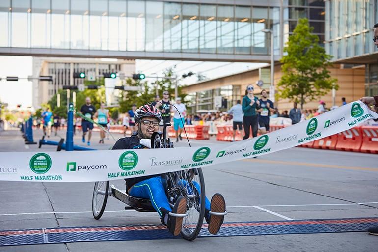 Man in wheelchair crossing the Oklahoma City Memorial Marathon finish line.