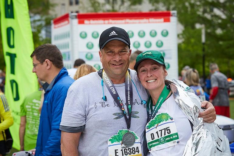 Man and woman runners celebrating at the Oklahoma City Memorial Marathon finish line.