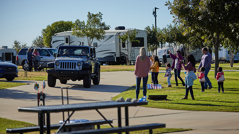 Group of people waving to jeep driving by at Fun Town RV Park at WinStar